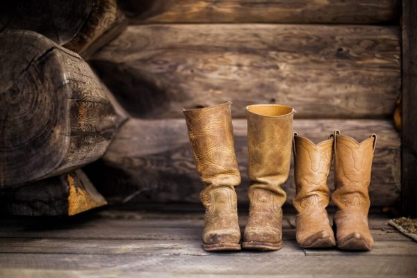 Two pairs, one big and one smaller, of rugged worn in leather cowboy boots on a barnwood floor.